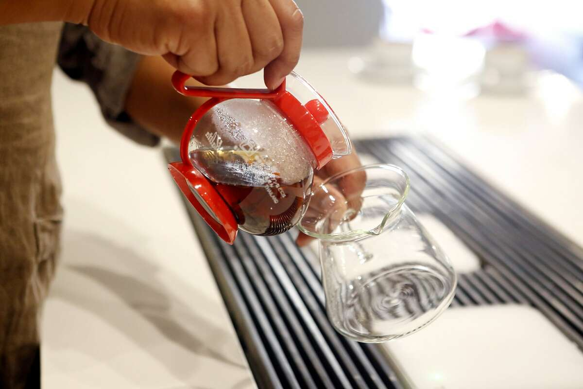 Nick Cho pours tea that steeped for four minutes as he creates at 'Karl the Latte' at Wrecking Ball Coffee in San Francisco Wednesday October 13, 2015.