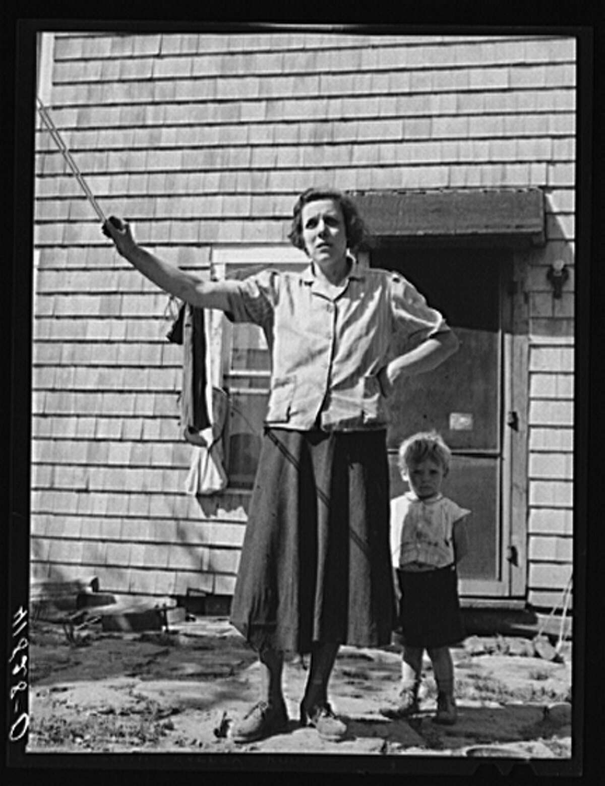 October 1940. Mrs. Thomas Festa and one of her children. FSA (Farm Security Administration) client, Italian, on the back porch of her house two miles out of Newtown, Connecticut