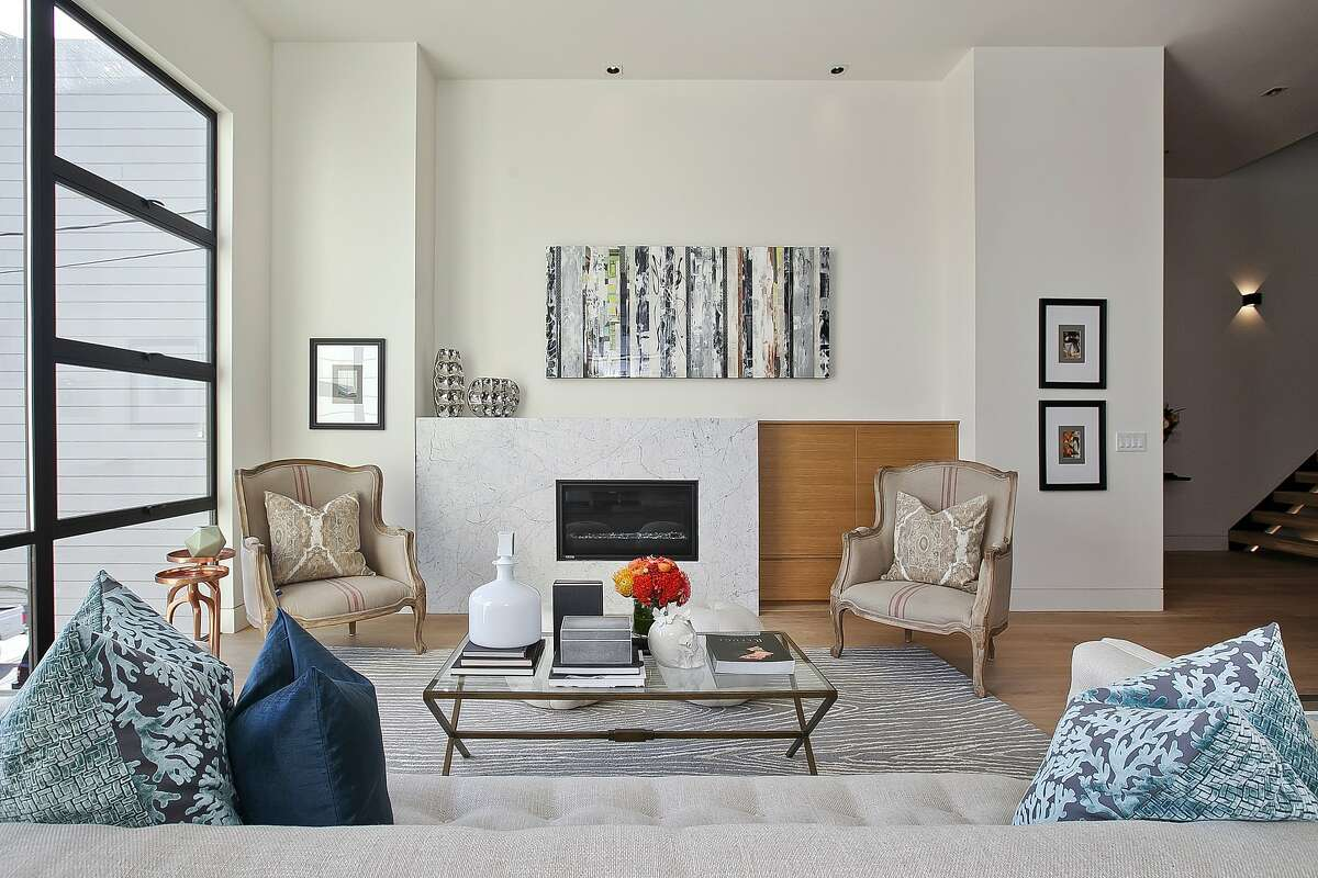 A chic gas fireplace with marble surround serves as a focal point in the living room of the remodeled Noe Valley home.