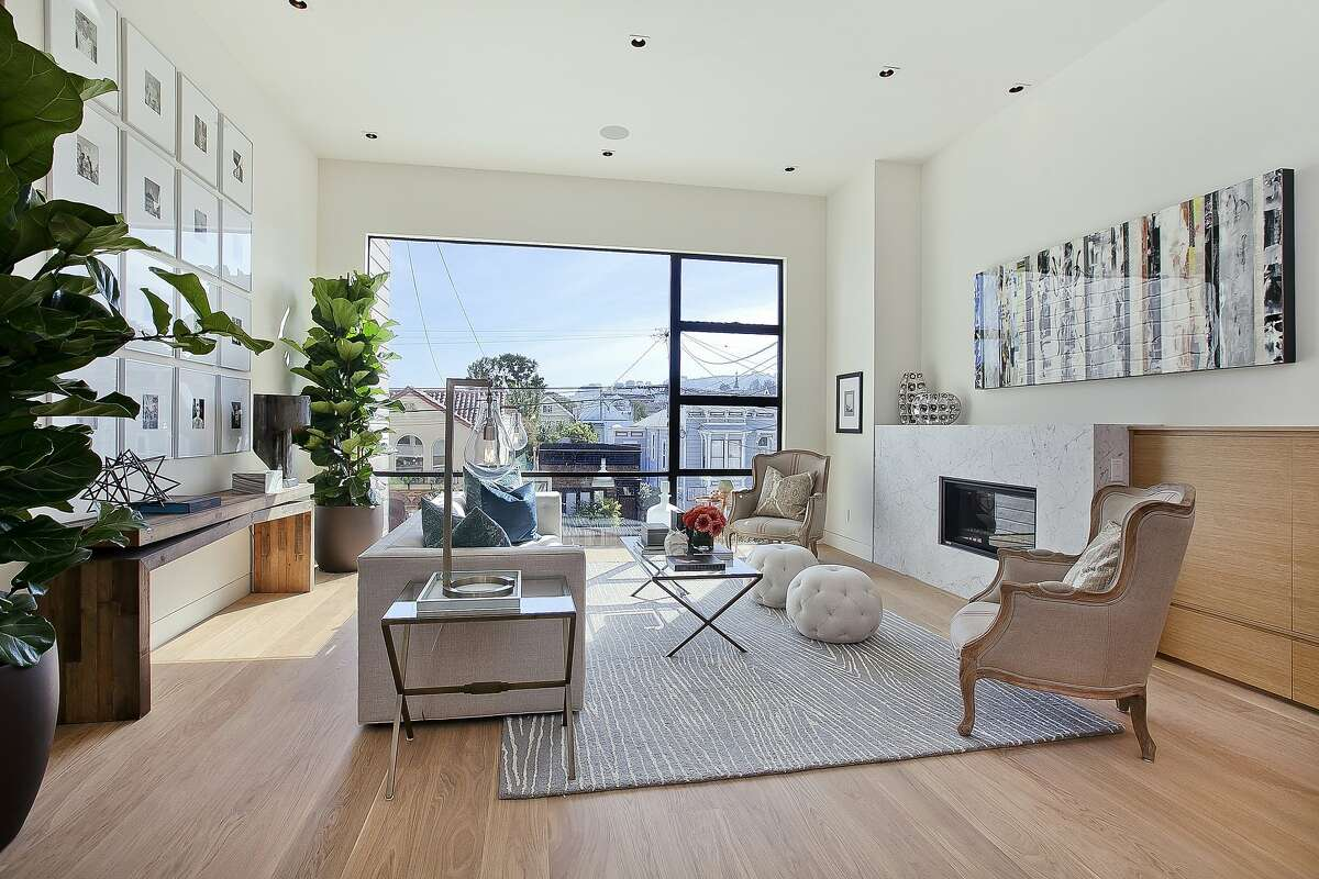 White oak flooring spans a living room with an oversized window overlooking the surrounding homes of Noe Valley.