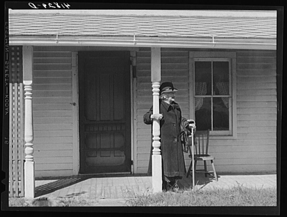 October 1940. Old woman waiting for a bus in front of her house. Newtown, Connecticut