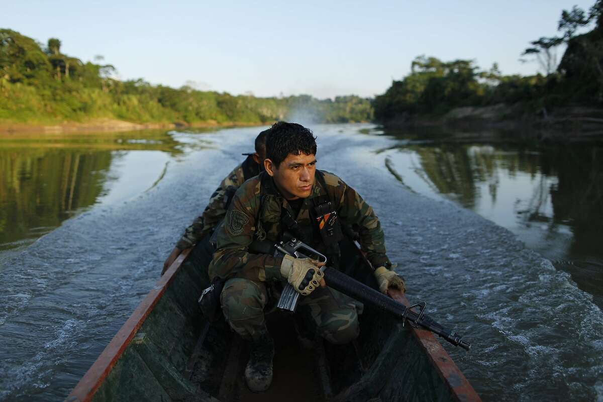 In this July 28, 2015 photo, counternarcotics police special forces cross a river on a boat after blowing a hole in a clandestine airstrip used by drug traffickers in Ciudad Constitucion, Peru. The country's narcotics police operate on a $12 million annual operating budget, with no planes or helicopters. (AP Photo/Rodrigo Abd)