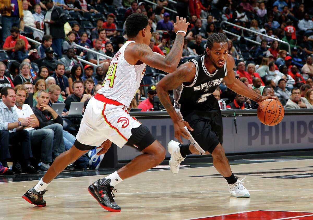 ATLANTA, GA - OCTOBER 14: Kawhi Leonard #2 of the San Antonio Spurs drives against Kent Bazemore #24 of the Atlanta Hawks at Philips Arena on October 14, 2015 in Atlanta, Georgia. NOTE TO USER User expressly acknowledges and agrees that, by downloading andor using this photograph, user is consenting to the terms and conditions of the Getty Images License Agreement. (Photo by Kevin C. Cox/Getty Images)