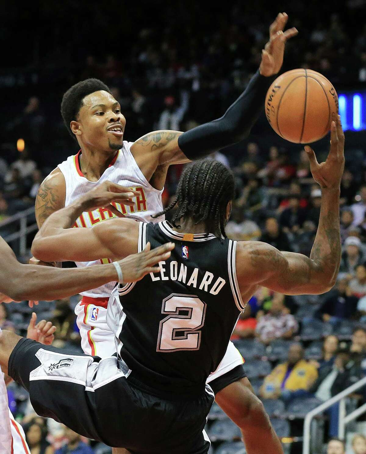 The Atlanta Hawks' Kent Bazemore fouls the San Antonio Spurs' Kawhi Leonard (2) on his way to the basket during the first period in a preseason game on Wednesday, Oct. 14, 2015, at Philips Arena in Atlanta. (Curtis Compton/Atlanta Journal-Constitution/TNS)
