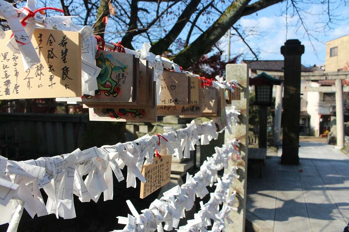 Ema blocks dangling in front of a shinto shrine in Kanazawa.