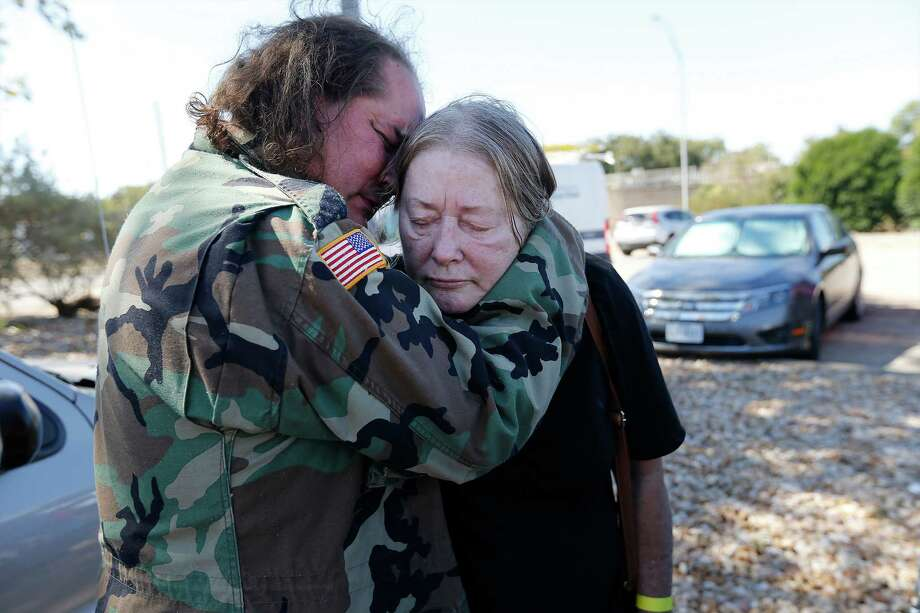 Smithville resident David Parrott consoles his weary and sleep-deprived mother, Sherry, over the loss of Sherry's home while awaiting to enter a shelter set up at the Smithville Recreation Center on Thursday, Oct. 15, 2015. Like the Parrotts, Bastrop County residents have dealt with evacuating their homes due to the Hidden Pines Fire. Firefighters continue to contain the flames that have now spread to more than 4,200 acres in Bastrop County according to the Texas A&M Forest Service. (Kin Man Hui/San Antonio Express-News) Photo: Kin Man Hui, Staff / San Antonio Express-News / ©2015 San Antonio Express-News