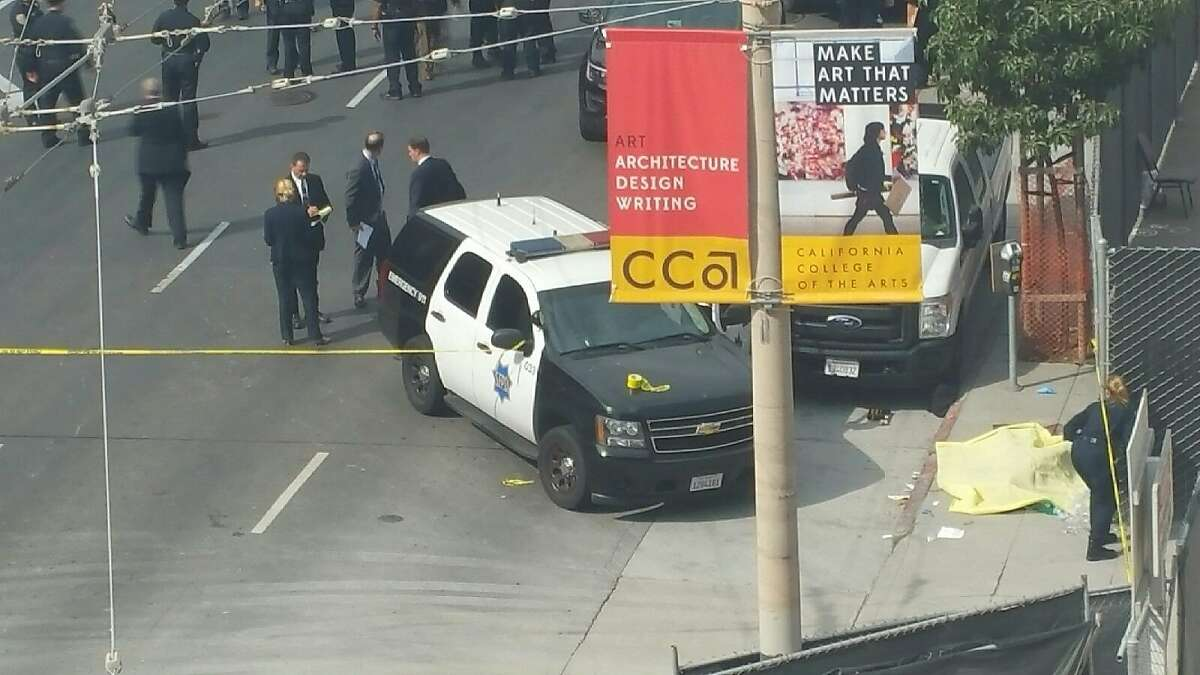 Detectives comb the scene of a fatal police-officer shooting on Eighth Street near Market Street Thursday while the man who was shot was lay on the sidewalk covered by a yellow tarp..