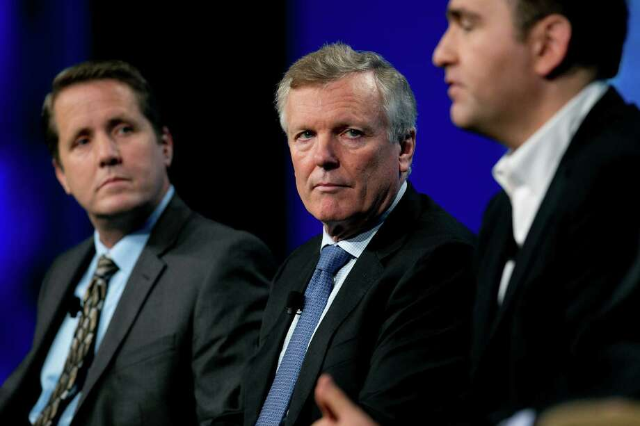 Charter Communications CEO Tom Rutledge, center, alongside Steve Shannon, general manager of content and services of Roku, left, in 2013 at the National Cable and Telecommunications Association Cable Show in Washington, D.C. Photo: Andrew Harrer / Bloomberg / © 2013 Bloomberg Finance LP