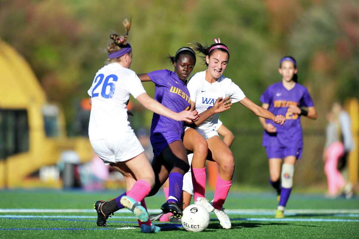 Westhill's Chelsea Domond, center, attemps to sneak past Darien defenders Megan Shanahan, left, and Charlotte Harmon during a Thursday afternoon varsity girls soccer game at Darien High School on Oct. 15, 2015.