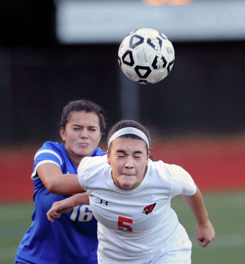 Foreground, Kimberly Kockenmeister (#5) of Greenwich heads the ball as Danbury's Taylor Izzo (#16) defends during the girls high school soccer match between Greenwich High School and Danbury High School at Greenwich, Conn., Thursday, Oct. 15, 2015. Photo: Bob Luckey Jr. / Hearst Connecticut Media / Greenwich Time