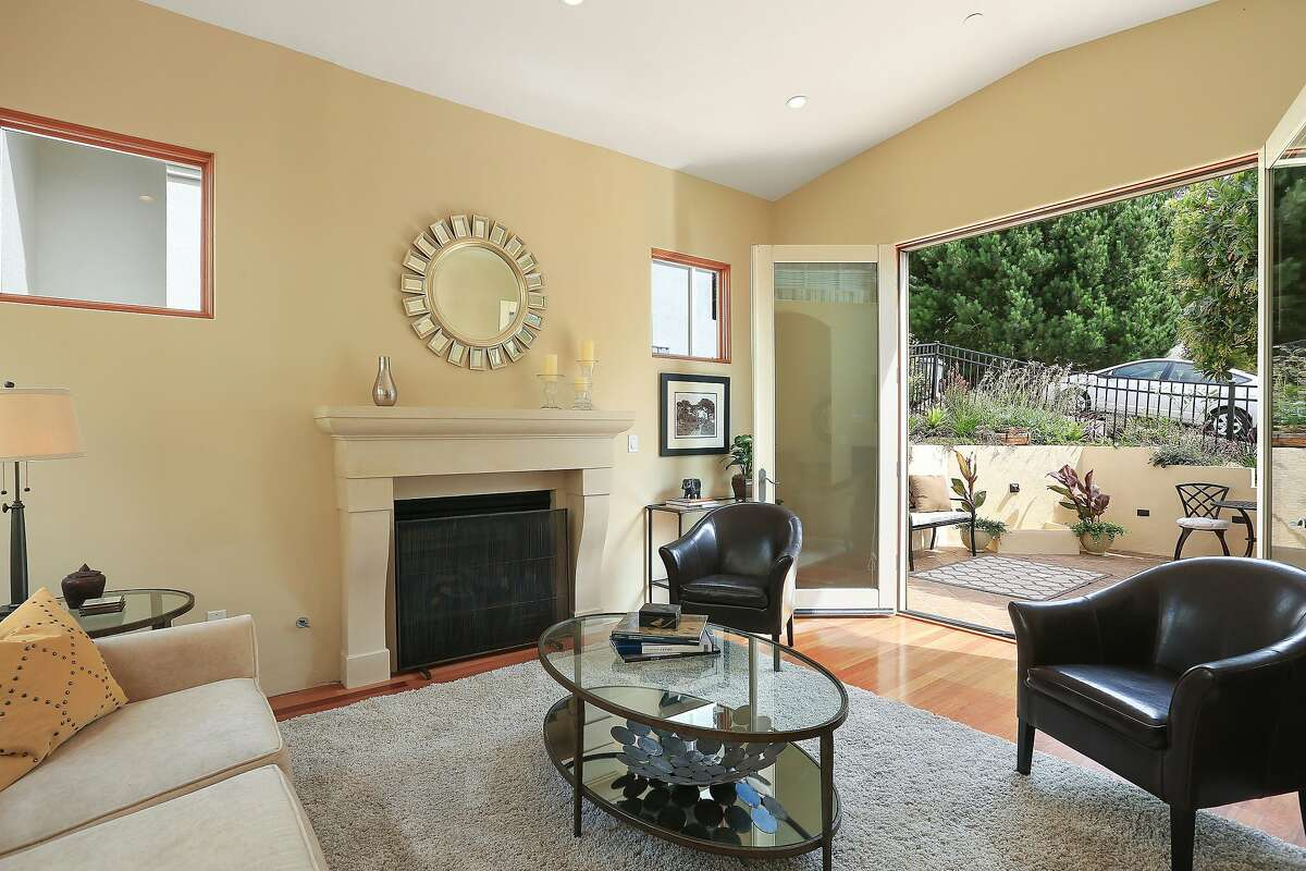 The living room opens to the front patio and includes a fireplace.