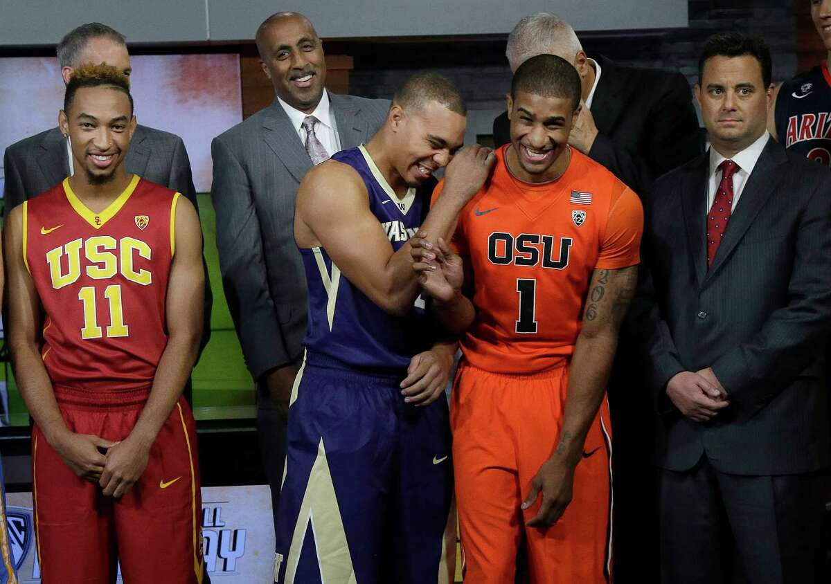 Washington's Andrew Andrews, center left, laughs with Oregon State's Gary Payton II before as they stand with Southern California's Jordan McLaughlin (11), Washington head coach Lorenzo Romar, center top, and Arizona head coach Sean Miller while posing for photos during NCAA college basketball Pac-12 media day in San Francisco, Thursday, Oct. 15, 2015. (AP Photo/Jeff Chiu)
