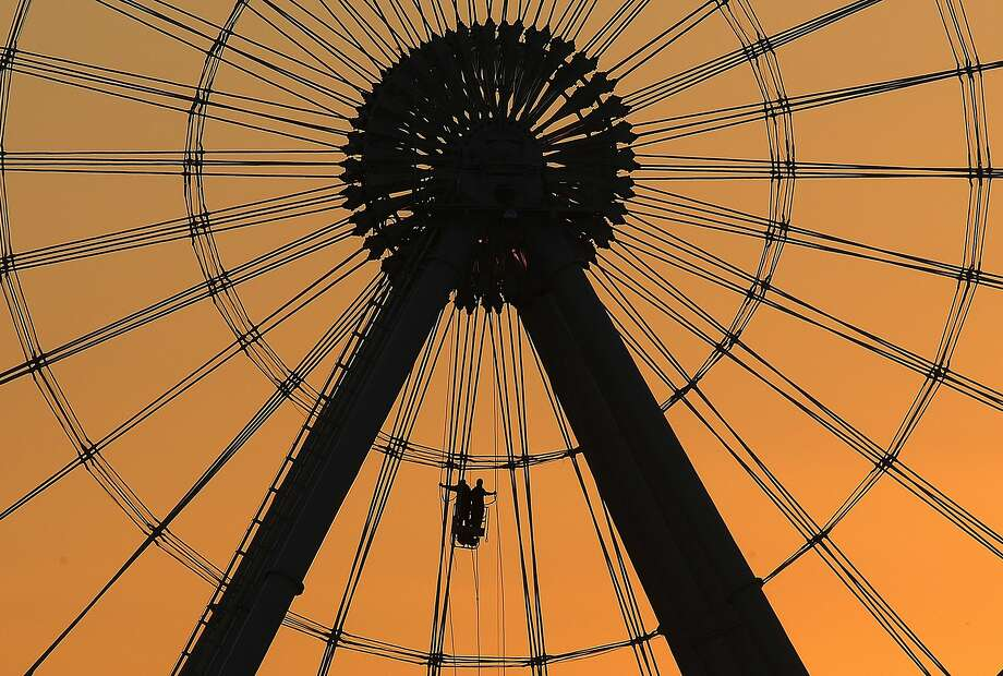 Dawn's early light is a backdrop as The Orlando Eye Technical Team use a device Thursday, Oct. 15, 2015 to conduct their daily visual inspection of the 400 foot tall observation wheel which is located off International Drive in Orlando. Photo: Red Huber, McClatchy-Tribune News Service