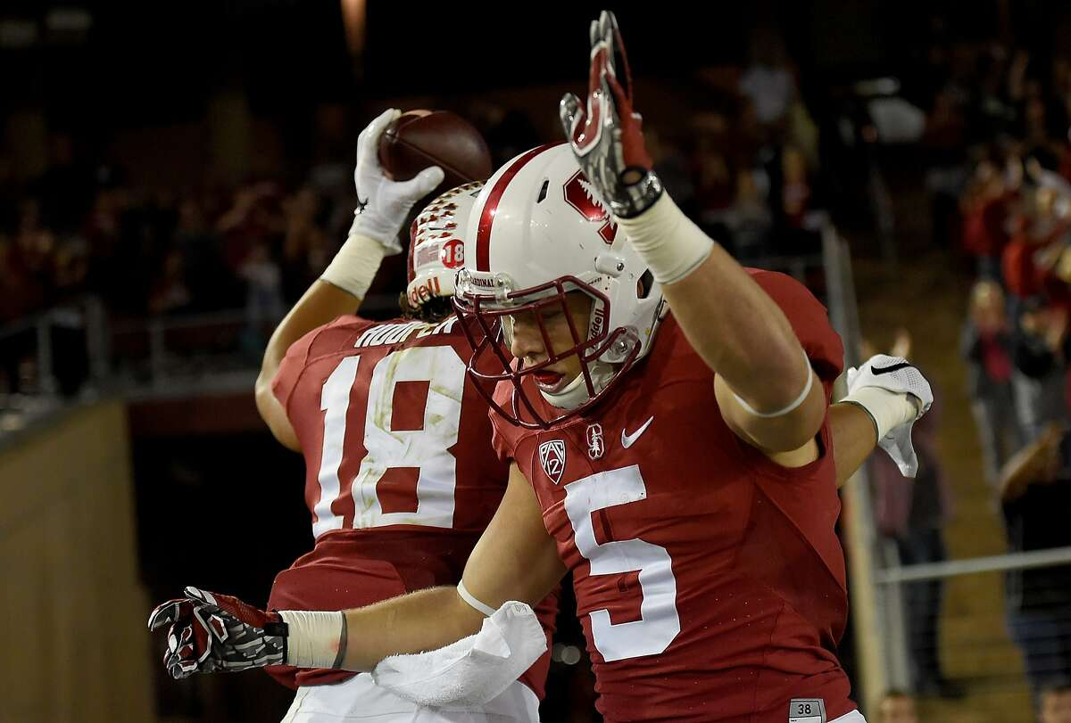 Austin Hooper #18 and Christian McCaffrey #5 of the Stanford Cardinal celebrate after Hooper caught a four yard touchdown pass against the UCLA Bruins in the first quarter at Stanford Stadium on October 15, 2015.