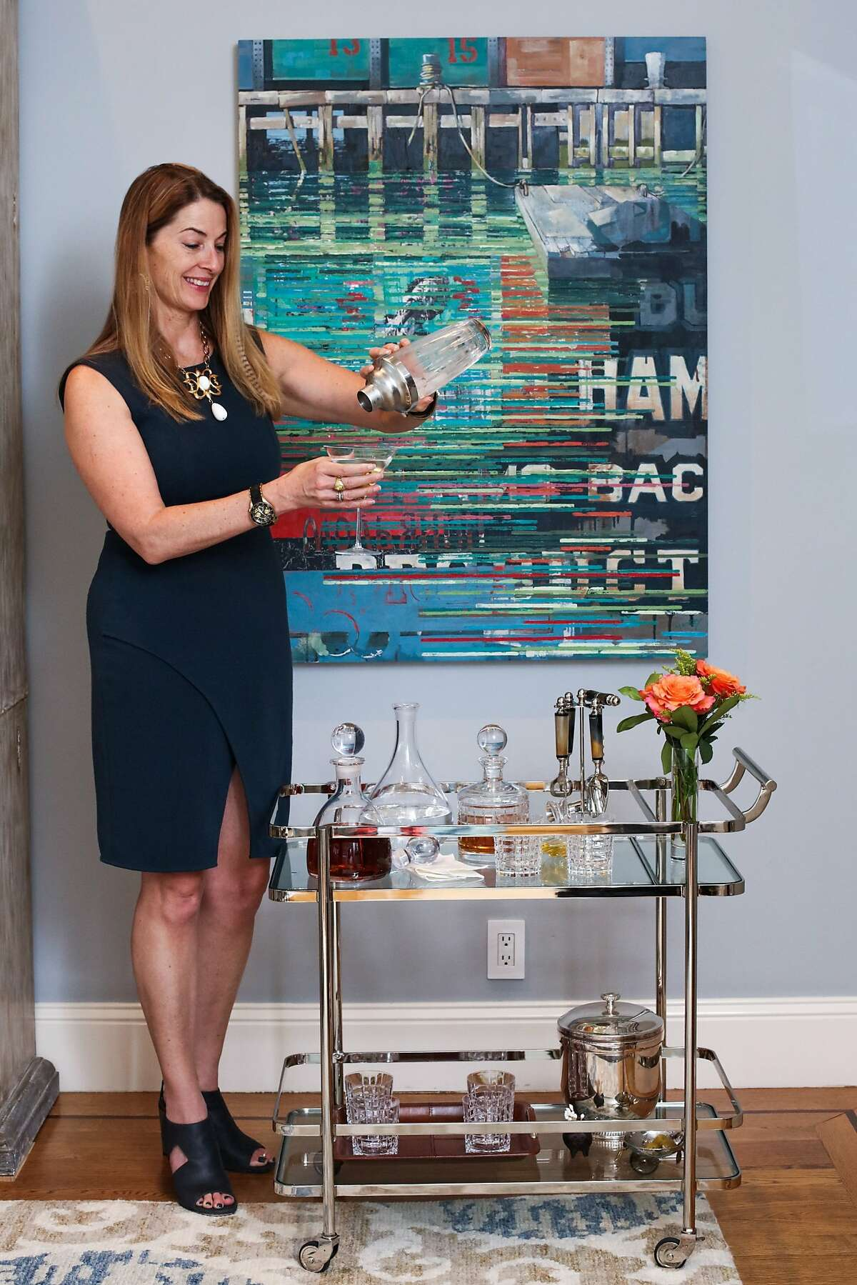 Interior designer Tineke Triggs pours a drink at the bar cart she arranged with a clean, uncluttered look in a client's home.