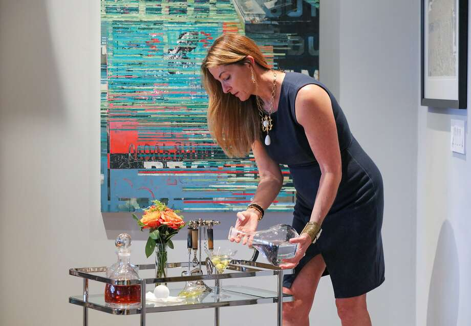 Interior designer Tineke Triggs pours a drink at the bar cart she arranged with a clean, uncluttered look in a client's home. Photo: Gabrielle Lurie, Special To The Chronicle