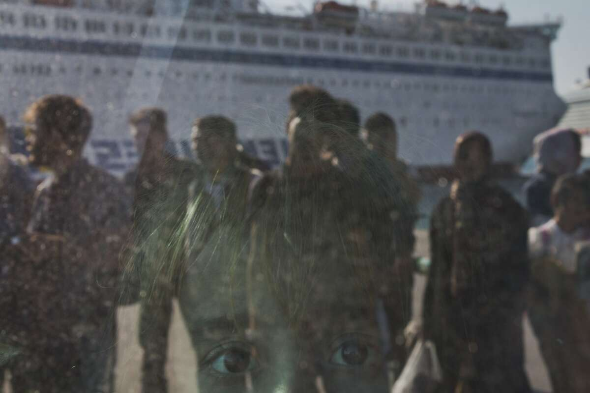 A child looks out from a window of a bus upon arriving by a ferry from the Greek island of Lesbos at the Athens' port of Piraeus on Thursday, Oct. 15, 2015. The international Organization for Migration said than more than 593,000 people have crossed into Europe this year - of which 453,000 traveled from Turkey to Greece, which has faced a massive influx of people from Syria.(AP Photo/Petros Giannakouris)