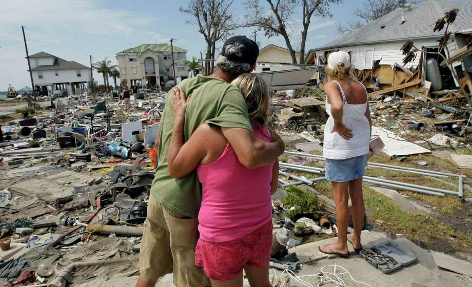 Wayne Neill, left, and Brenda Roby, center, hug as Donna Hanson looks over the debris left where her home once stood in the the aftermath of Hurricane Ike Wednesday, Sept. 24, 2008 in Galveston, Texas. Residents were allowed to return to the island Wednesday. (AP Photo/David J. Phillip) Photo: David J. Phillip, STF / AP / AP