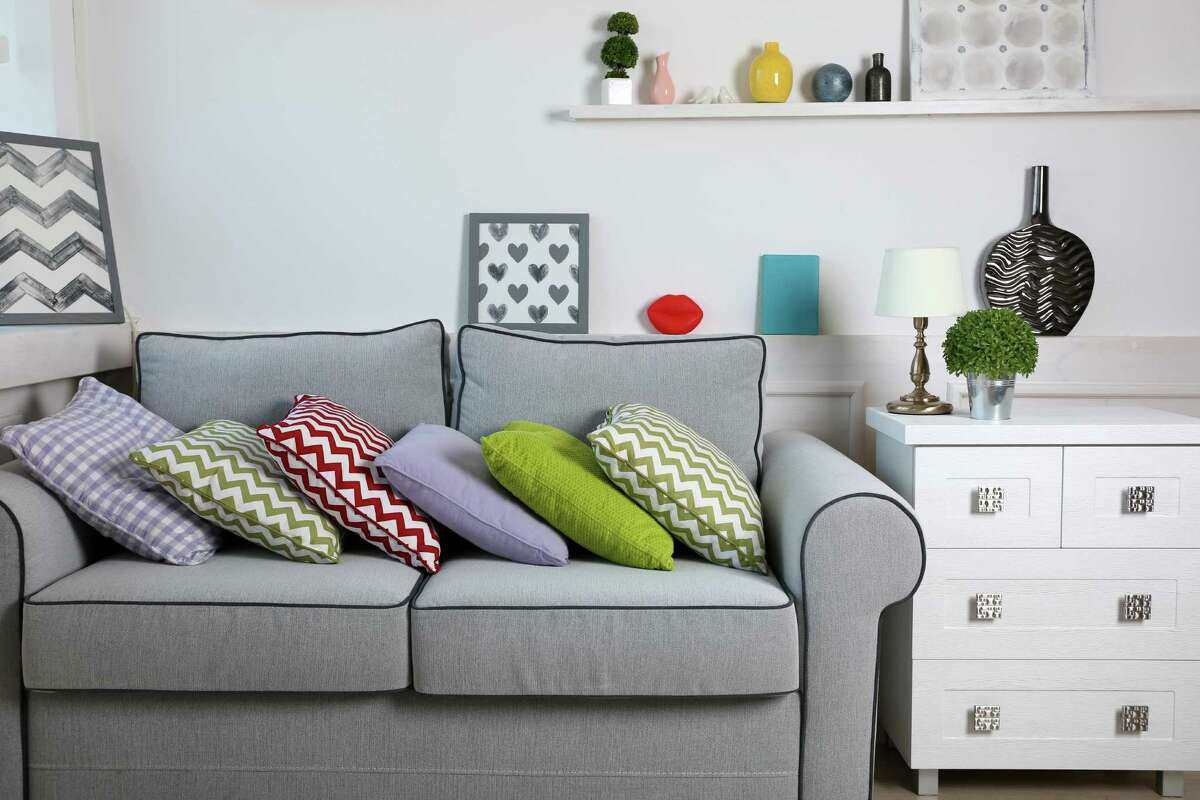 Modern living room with grey sofa and various colored accents pillows. (Fotolia)