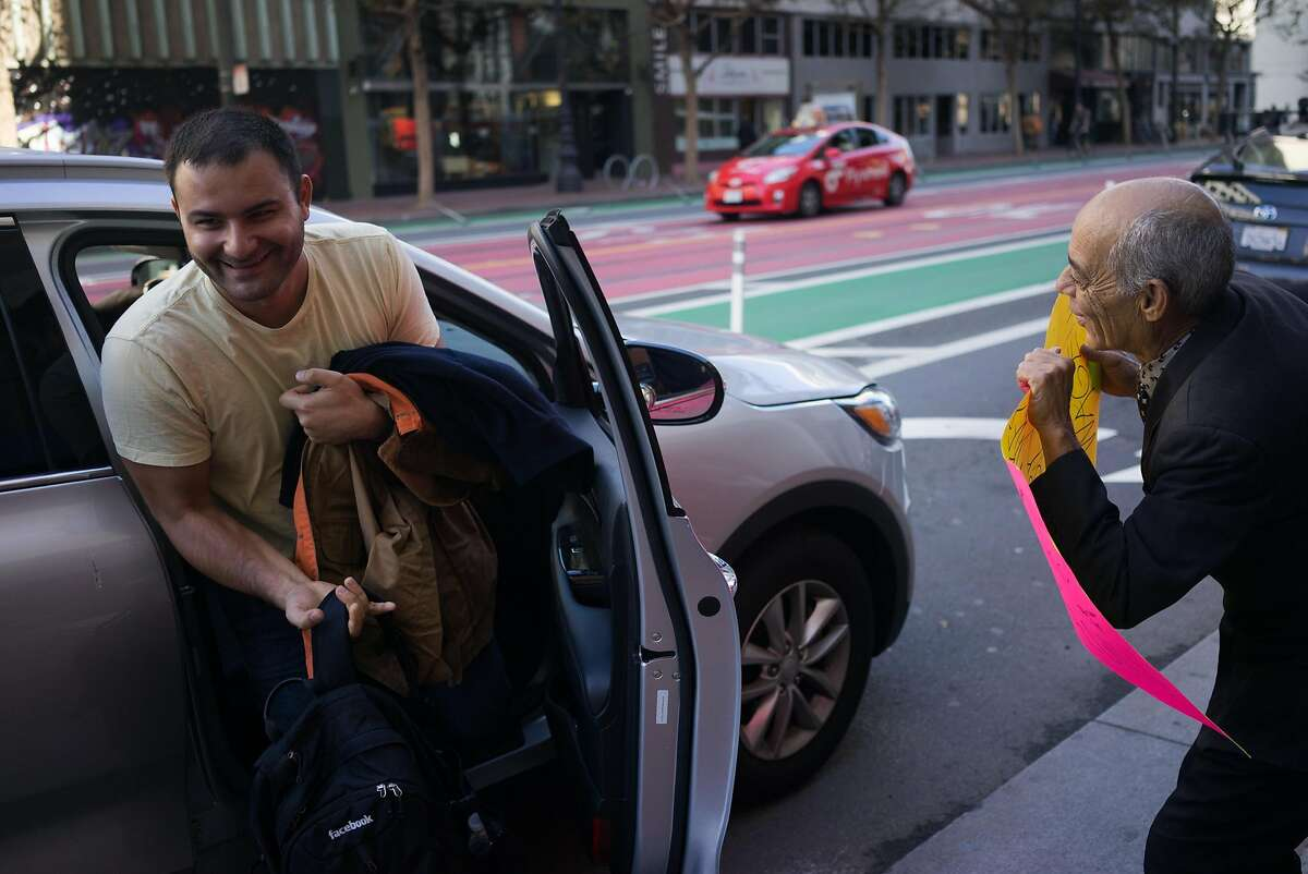 Jorge Cordero Valedez, right, protests as a man gets out of an Uber in front of Uber Headquarters in San Francisco , Calif. on Friday, Oct. 16, 2015. Some Uber drivers will partake in a nationwide strike this weekend.