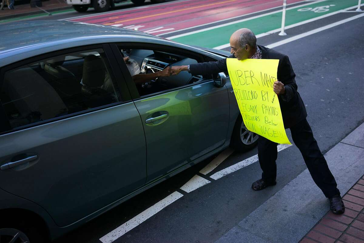 Jorge Cordero Valdez fist bumps an Uber driver as he protests in front of Uber headquarters in San Francisco , Calif. on Friday, Oct. 16, 2015. Some Uber drivers will partake in a nationwide strike this weekend.