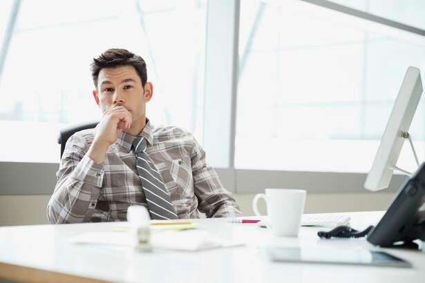 Portrait of businessman sitting at desk in office