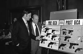 """FILE - In this Wednesday, April 23, 1975 file photo, Sen. Birch Bayh, D-Ind., left, chairman of the Senate judiciary subcommittee on juvenile delinquency, and David MacDonald, assistant secretary of treasury, look over a display of guns prior to hearings on gun control in Washington. Republican President Richard Nixon also favored gun control. Bayh says that the NRA helped prevent his 1972 bill banning """"Saturday night special"""" handguns from getting through Congress. (AP Photo/Henry Griffin)"""