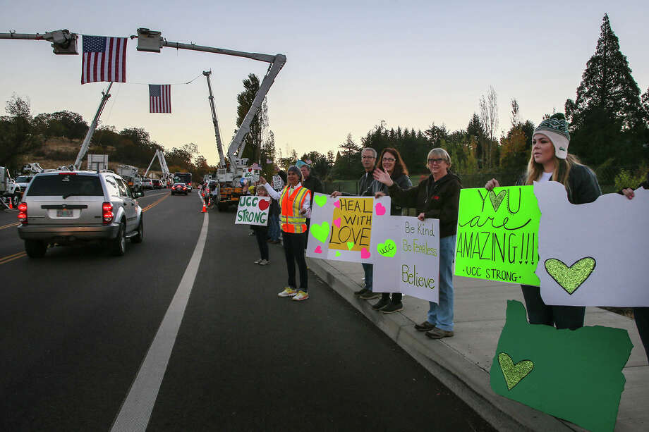 People gather at the entrance of Umpqua Community College in Roseburg, Ore., to support the students and faculty in their return to classes for the first time since the Oct. 1 shooting on campus. A reader says the only way to address the gun problem in this country is by requiring gun permits. Photo: Mary Jane Schulte /Associated Press / The Register-Guard