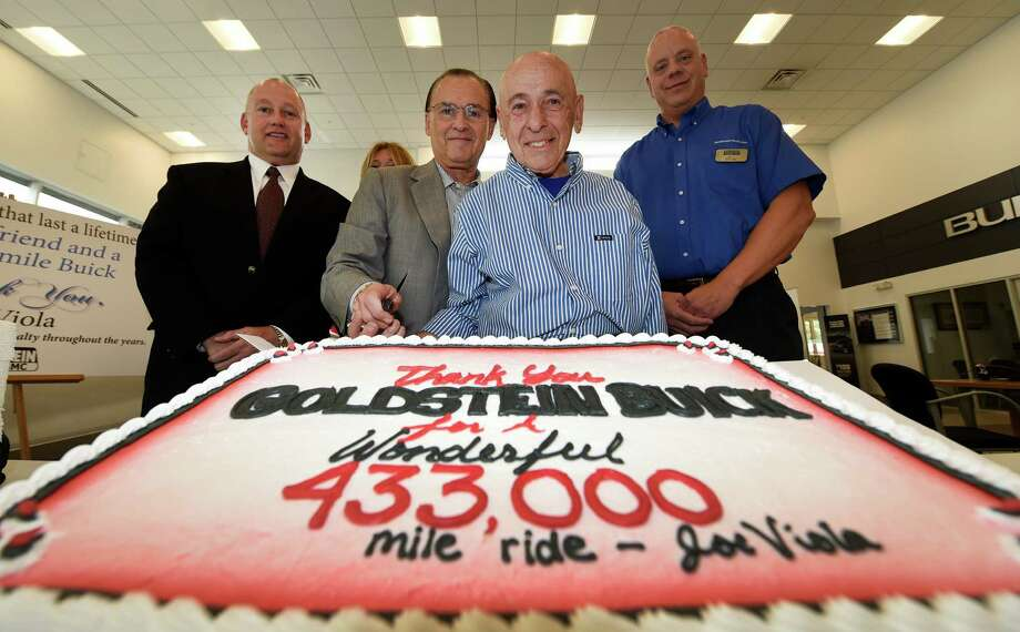 Joe Viola, second from right, cuts a cake he brought to Goldstein Buick at the trade-in ceremony for his 2003 Buick Rendezvous with 433,619 miles on the odometer Wednesday Oct. 14, 2015, in Colonie, N.Y. Joining Viola at the cake cutting is, from left; Greg Goldstein, Alan Goldstein, Viola and service manager Jeff Stone. (Skip Dickstein/Times Union) Photo: SKIP DICKSTEIN / 10033748A