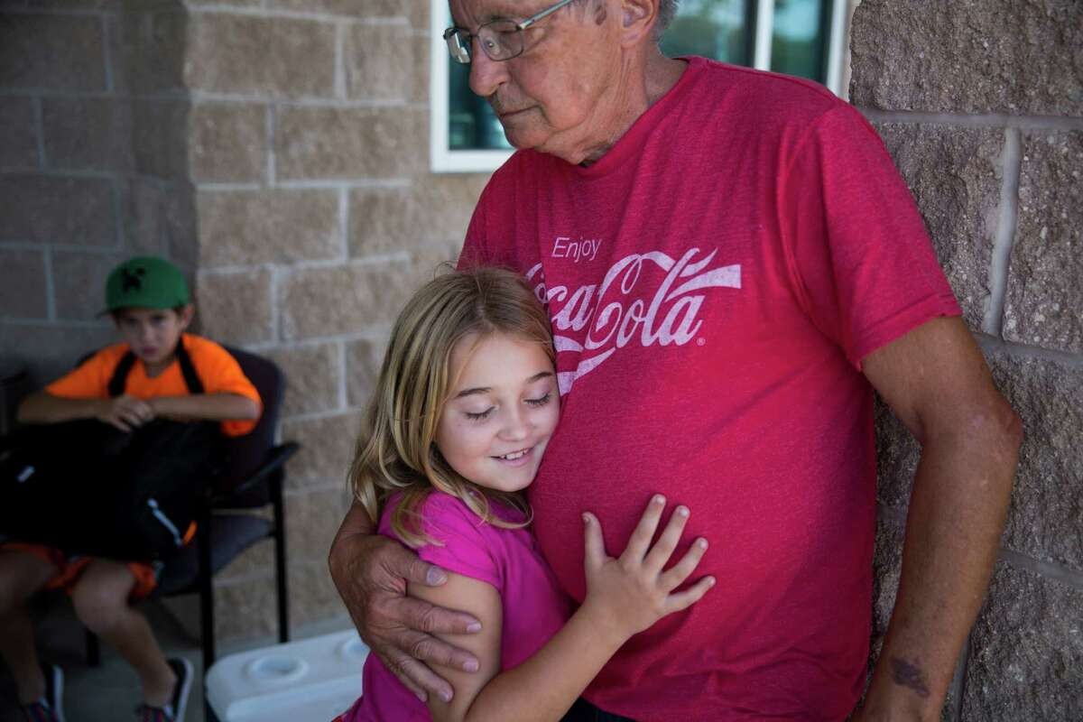 Ayla Witt, 13, hugs her grandfather Pat Andrews outside of the Red Cross Shelter for evacuees of the fire set up in the Smithville Recreation Center in Smithville, Texas on October 16, 2015. They were evacuated from their home for the fire, but their home survived. In 2011, they lost their home in a fire, so this time Witt's mother Laura Witt said that they feel they were