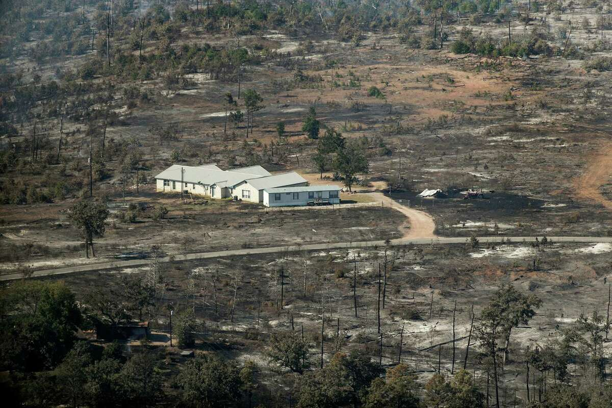 In this aerial photo, a home surrounded by burned landscape appearsspared from the Hidden Pines Fire near Smithville, Texas, Friday, Oct. 16, 2015. A preliminary investigation indicates a farming accident sparked the wildfire that's consumed more than 7 square miles and destroyed 40 structures in Central Texas, authorities said Friday. (Rodolfo Gonzalez/Austin American-Statesman via AP) AUSTIN CHRONICLE OUT, COMMUNITY IMPACT OUT, INTERNET AND TV MUST CREDIT PHOTOGRAPHER AND STATESMAN.COM, MAGS OUT; MANDATORY CREDIT