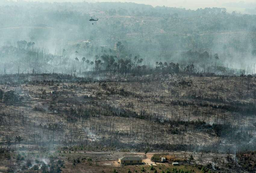 In this aerial photo, a National Guard helicopter uses a bucket to drop water on the Hidden Pines Fire near Smithville, Texas, Friday, Oct. 16, 2015. A preliminary investigation indicates a farming accident sparked the wildfire that's consumed more than 7 square miles and destroyed 40 structures in Central Texas, authorities said Friday. (Rodolfo Gonzalez/Austin American-Statesman via AP) AUSTIN CHRONICLE OUT, COMMUNITY IMPACT OUT, INTERNET AND TV MUST CREDIT PHOTOGRAPHER AND STATESMAN.COM, MAGS OUT; MANDATORY CREDIT
