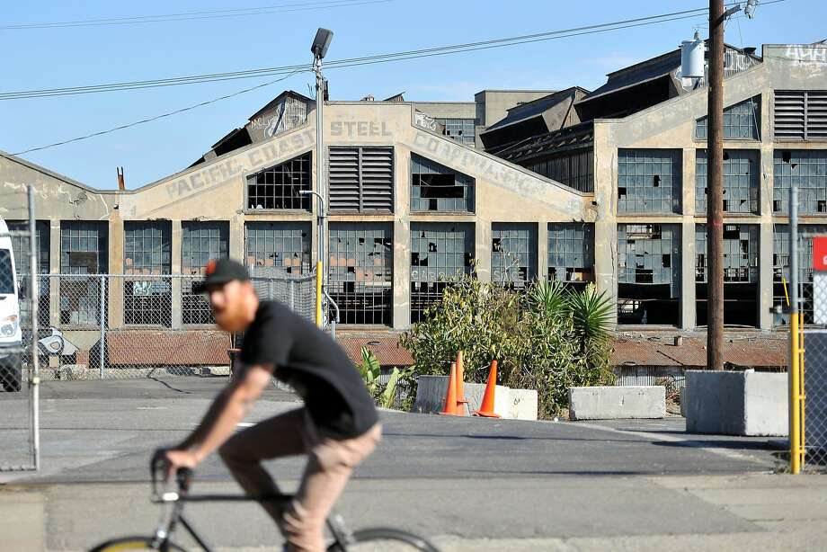 A bicyclist passes by an old steel building in the dogpatch neighborhood of San Francisco in October. Photo: JOSH EDELSON / SAN FRANCISCO CHR