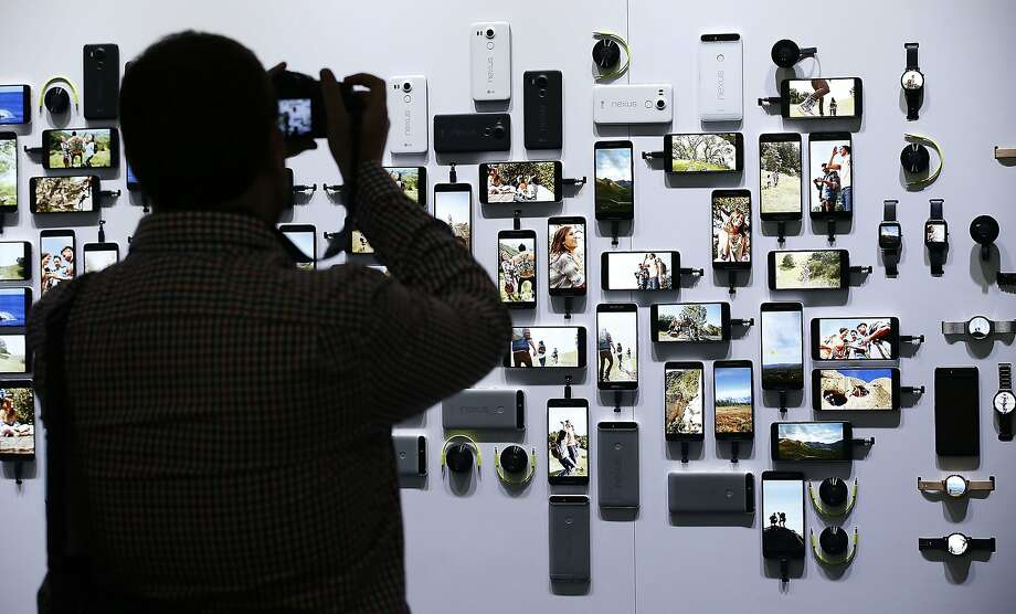 "A reporter takes a picture of new Google devices on display during a Google event on Tuesday, Sept. 29, 2015, in San Francisco. Google is countering the release of Apple's latest iPhones with two devices running on ""Marshmallow,"" a new version of Android software designed to steer and document even more of its users' lives. (AP Photo/Tony Avelar) Photo: Tony Avelar, Associated Press"