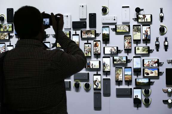 "A reporter takes a picture of new Google devices on display during a Google event on Tuesday, Sept. 29, 2015, in San Francisco. Google is countering the release of Apple's latest iPhones with two devices running on ""Marshmallow,"" a new version of Android software designed to steer and document even more of its users' lives. (AP Photo/Tony Avelar)"
