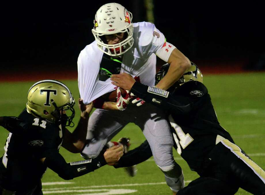 Trumbull's Stephen Nagy, left, and Trevor Bellows, right, tackle Greenwich's Luke Bienstock during high school football action in Trumbull, Conn. on Friday October 16, 2015. Photo: Christian Abraham, Hearst Connecticut Media / Connecticut Post