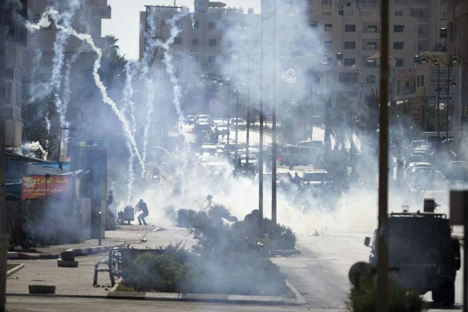 Israeli troops fire tear gas during clashes with Palestinians near Ramallah, West Bank. Seven Israelis have been killed in more than two dozen attacks by Palestinians this month. Photo: Majdi Mohammed /Associated Press / AP