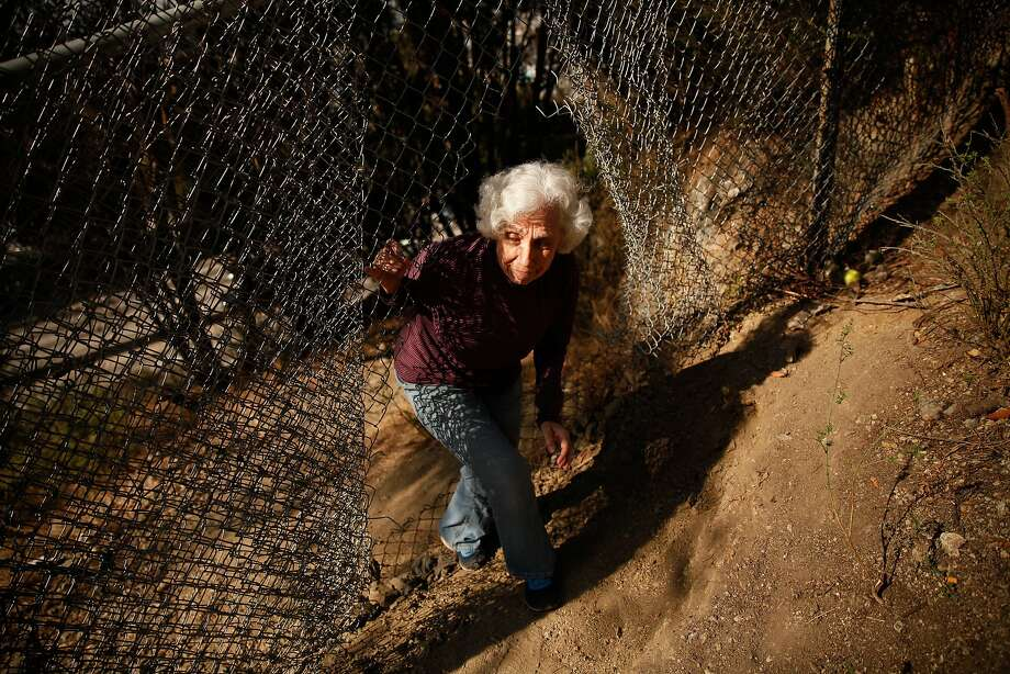 Jean Bogiages, a resident of Potrero Hill, goes through a hole in the fence many homeless use to access the hill over Highway 101 where they camp in San Francisco. Photo: Sarah Rice, Special To The Chronicle