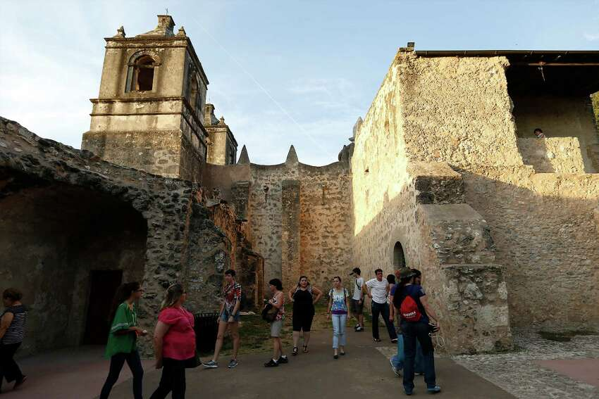 Guests take a walking tour outside Mission Concepcion as part of the World Heritage Site Celebrations on Friday, Oct. 16, 2015. The San Antonio Office of Historic Preservation hosted the event which featured a light projection on the mission of how it originally looked according to officials. Guests were also treated to tours around the mission, music and food.