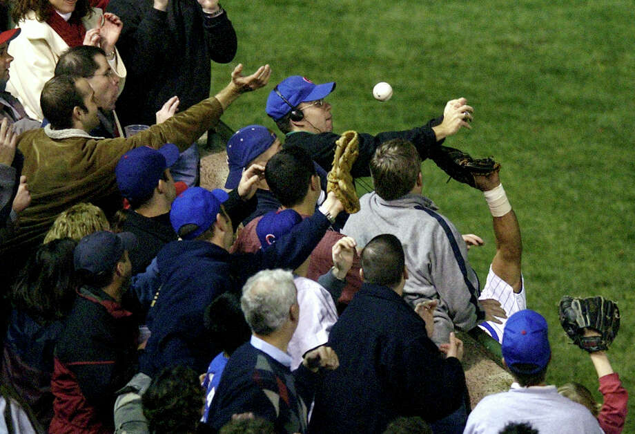 An ill-fated attempt by Steve Bartman (wearing headphones) to catch a foul ball during the 2003 NLCS is a reminder for Cubs fans of the club's blown opportunity to reach the World Series that year. Photo: Morry Gash, STF / AP