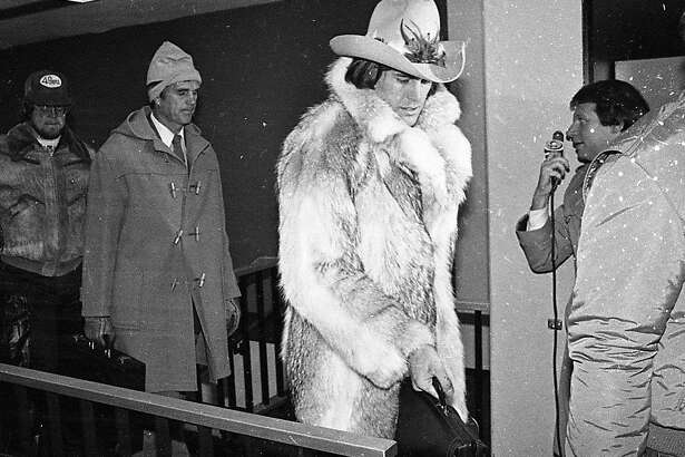 San Francisco 49ers wide receiver Dwight Clark departs the team plane in Detroit in a glorious fur coat on the way to Super Bowl XVI. Jan. 20, 1982.