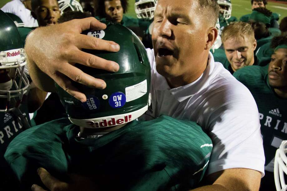 Spring Lions' head coach Sam Parker hugs defensive lineman Joseph Dorceus (94) after the victory over Montgomery in a high school football game at George Stadium on Friday, October 16, 2015, in Spring. Both Parker and Dorceus served a one game suspension last week. Photo: Joe Buvid, For The Chronicle / © 2015 Joe Buvid
