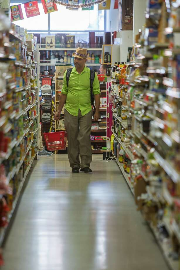 Nils Heyman shops last week at the Duc Loi Market in the Mission. Duc Loi, which specializes in Asian and Latin American food, will open a second store in the Bayview. Photo: Nathaniel Y. Downes, The Chronicle