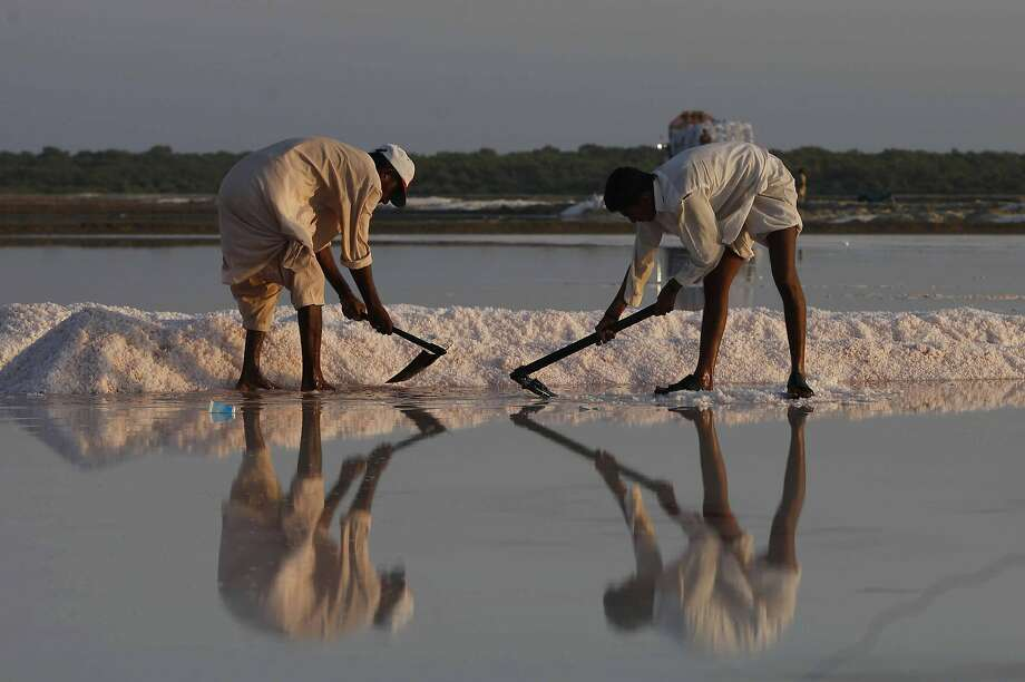 Pakistani laborers collect sea salt at a coastal area near Karachi, Pakistan, Friday, Oct. 16, 2015. They earn average 600 Pakistani rupees (US$ 6) per day for their work to earn living for families. Photo: Shakil Adil, Associated Press