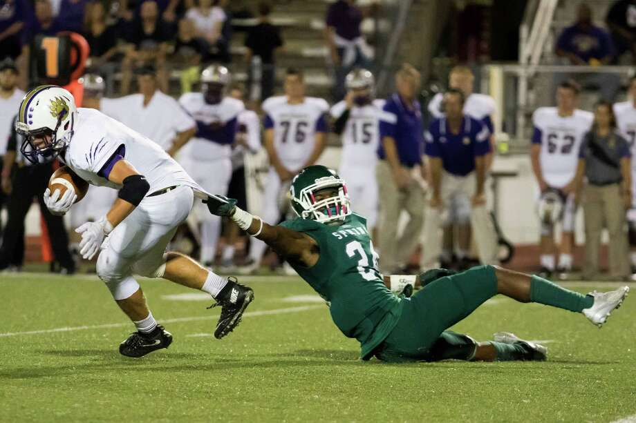 Spring linebacker Tyrek Domio is hanging by a thread as he tries to bring down Montgomery running back Alex Nunn, who spins away from Domio to pick up a first down in the second quarter of the Lions' District 15-6A 25-20 victory over the Bears at George Stadium. Photo: Joe Buvid, Freelance / © 2015 Joe Buvid