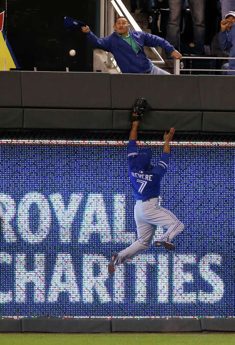 Blue Jays left fielder Ben Revere comes up way short in his attempt to get a glove on a ball hit by the Royals' Salvador Perez that went for a solo home run during the fourth inning Friday night in Kansas City, Mo. The Royals won 5-0 to take a 1-0 lead in the best-of-seven American League Championship Series. Photo: Matt Slocum, STF / AP