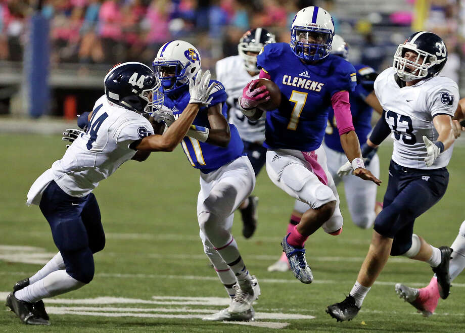 Clemens' Frank Harris (center) heads to the end zone for a touchdown as Smithson Valley's Trevon Moehrig-Woodard (left) is blocked by Clemens' Tommy Bush and Smithson Valley's Jack Gibbens moves in on the play during second half action on Oct. 16, 2015 at at Lehnhoff Stadium. Clemens won 57-56. Photo: Edward A. Ornelas /San Antonio Express-News / © 2015 San Antonio Express-News