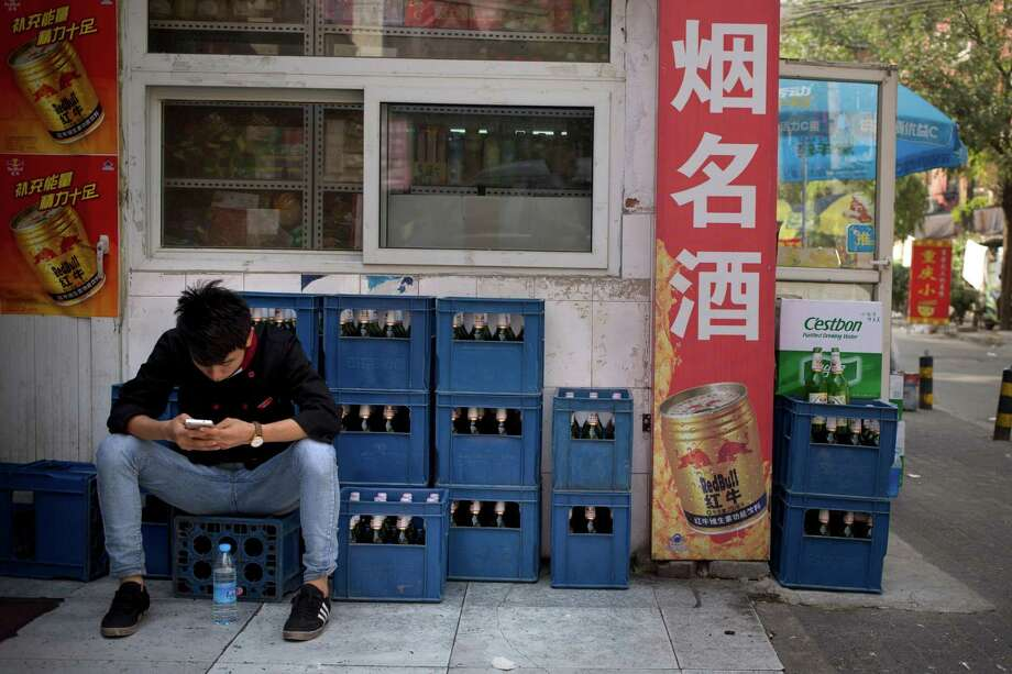 In this Thursday, Oct. 15, 2015 photo, a restaurant worker sits on crates of beer outside a convenience store as he uses his smartphone in Beijing. A potential prize for AB InBev in its bid for SABMiller is a Chinese beer, Snow, that is the world's biggest seller. But any deal will face Chinese regulators who have barred the two brewing giants in the past from cooperating. (AP Photo/Mark Schiefelbein) Photo: Mark Schiefelbein, STF / AP