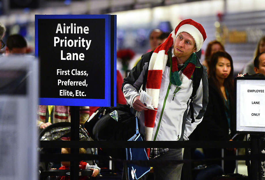 Amos Darnell looks for a shorter line at a security checkpoint in Charlotte, N.C., during last year's holiday season.  Photo: Todd Sumlin, MBI / The Charlotte Observer