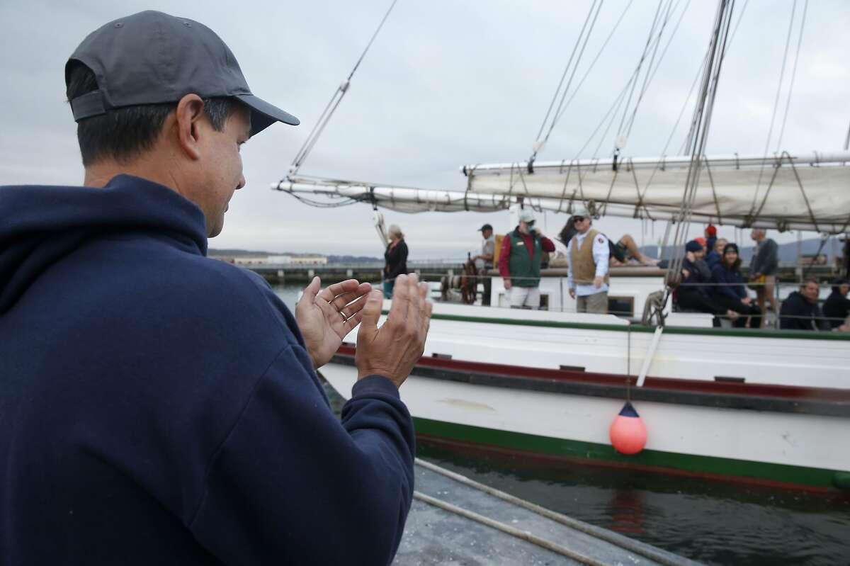 Dolphin Club president Rick Avery applauds race competitors as the Alma departs the Hyde Street Pier to ferry them to Alcatraz for the swimming leg of the Escape From Alcatraz triathlon at Aquatic Park in San Francisco, Calif. on Saturday, Oct. 17, 2015. Organizers took extra precautions for this year's event, including additional pilot boats, after great white shark sightings in the bay in recent weeks.
